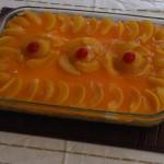 Cheesecake con salsa de naranja y melocotones
